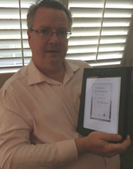 El Paso Times Editor Bob Moore shows a biography of Thomas Jefferson he's reading on his iPad.