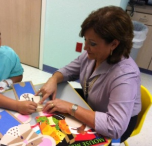 United Way Board Chair Janet Aguilar of Wells Fargo reads at the Providence Children's Hospital